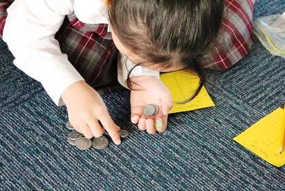 Young girl counting coins on blue carpet